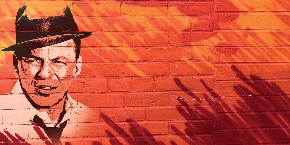 Bild av Frank Sinatra på orange tegelvägg.